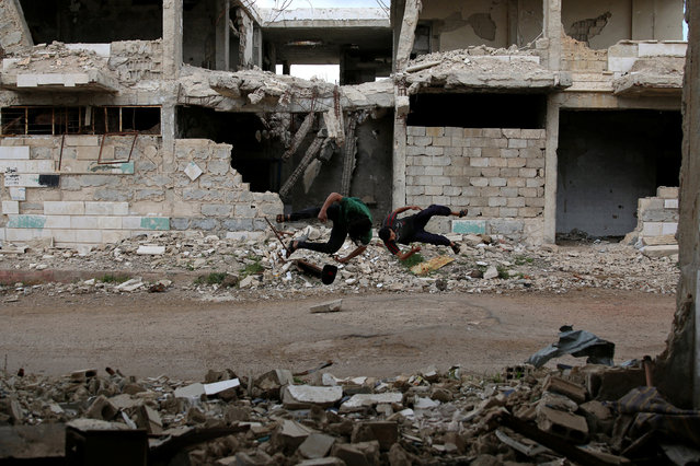 Parkour coach Ibrahim al-Kadiri (L), 19, and Muhannad al-Kadiri, 18, demonstrate their Parkour skills in the rebel-held city of Inkhil, west of Deraa, Syria, April 7, 2017. Members of the group say Parkour takes them away from the atmosphere of war and helps them to take their sorrows away. It unloads their negative energy. (Photo by Alaa Al-Faqir/Reuters)
