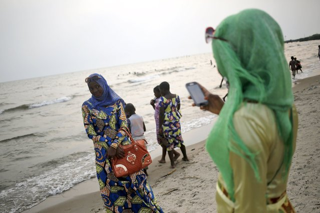 Women pose for cell phone pictures on a beach on the shores of Lake Tanganyika in Burundi's capital Bujumbura as the country awaits next week's presidential elections, July 18, 2015. Opposition politicians have accused Burundi's President Pierre Nkurunziza of violating the constitution by running for a third term and are boycotting the vote due on July 21. Dozens of people have already died in protests in the world's third poorest country which emerged from civil war in 2005. (Photo by Mike Hutchings/Reuters)