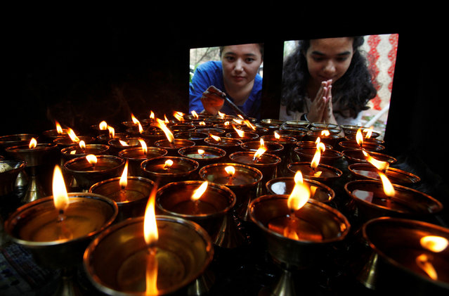 Devotees offer prayers next to oil lamps at a Buddhist temple on the occasion of Buddha Purnima festival, also known as Vesak Day, in Chandigarh, India, May 10, 2017. (Photo by Ajay Verma/Reuters)