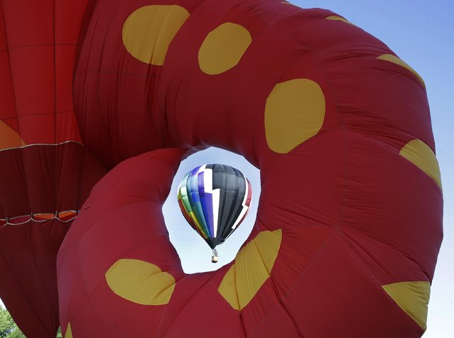 An inflated hot air balloon is seen through the tail of large seahorse character hot air balloon during the 33rd annual QuickChek New Jersey Festival of Ballooning at Solberg Airport Friday, July 24, 2015, in Readington, N.J. (Photo by Mel Evans/AP Photo)
