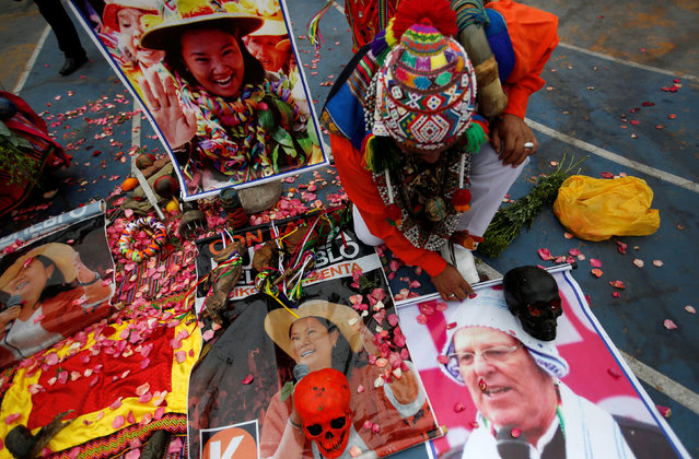 Peruvian shamans with posters of presidential candidates Keiko Fujimori and Pedro Pablo Kuczynski perform a ritual of predictions prior to elections in Lima, Peru, May 30, 2016. (Photo by Mariana Bazo/Reuters)