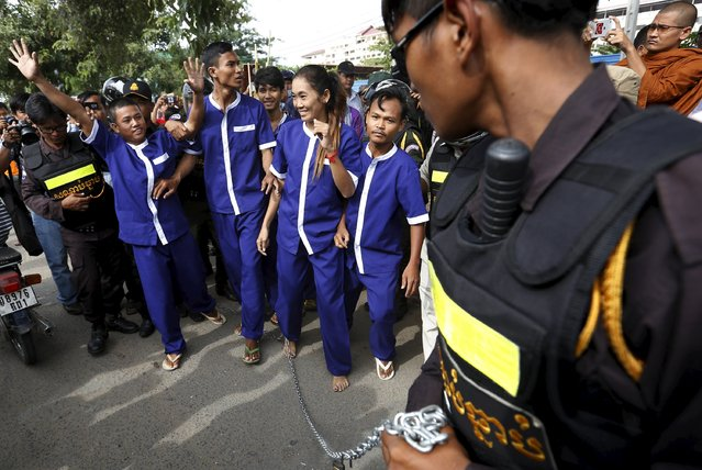 Police officers detain protesters who tied themselves with long chains to their feet and wore prison uniforms during a protest in front of the Cambodia National Assembly in Phnom Penh, July 26, 2015. Cambodia passed a contentious law to regulate non-governmental organisations (NGOs) which government critics fear will be used to muzzle opposition. (Photo by Samrang Pring/Reuters)