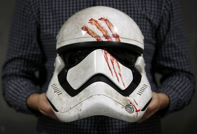 "A worker holds a replica of Finn's Stormtrooper helmet from ""Star Wars: The Force Awakens"", in the Propshop headquarters at Pinewood Studios near London, Britain May 25, 2016. (Photo by Peter Nicholls/Reuters)"