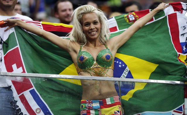A spectator poses with her festive attire before the group A World Cup soccer match between Cameroon and Croatia at the Arena da Amazonia in Manaus, Brazil, Wednesday, June 18, 2014. (Photo by Marcio Jose Sanchez/AP Photo)