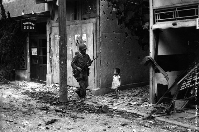 An American soldier patrolling the streets of Inchon after the capture of this key port during the Korean war, is watched by a young Korean child, 1950