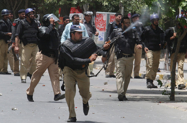A Pakistani police officer fires his rifle in the air to disperse protestors during clashes in Lahore, Pakistan, Tuesday, June 17, 2014. Police clashed Tuesday with followers of an anti-Taliban cleric critical of Pakistan's government in the eastern city of Lahore, violence that killed at least five people, officials said. (Photo by K.M. Chaudary/AP Photo)