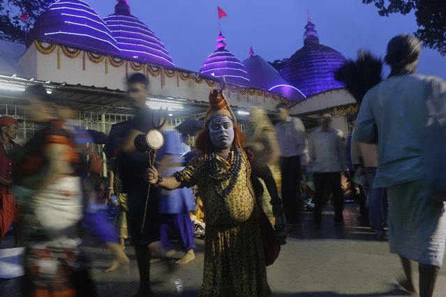 An Indian man stands dressed like Hindu god Shiva to attract alms from devotees during the Ambubasi festival at the Kamakhya Hindu temple in Gauhati, India, Sunday, June 22, 2014. The annual festival where hundreds of holy men from an esoteric form of Hinduism, gather to perform rituals at the temple begins on June 22. (Photo by Anupam Nath/AP Photo)