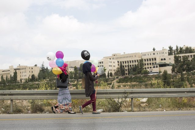 Palestinians carry balloons while making there way to the opening ceremony of Palestinian Museum for Arts and History, in West Bank town of BirZeit, north of Ramallah, 18 May 2016. The $30 million Palestinian Museum contemporary building aims to redefine the Palestinian art, history and culture. (Photo by Atef Safadi/EPA)