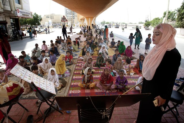 Pakistani volunteer Syeda Anfas Zaidi teaches students at a make shift school under a bridge in Karachi, Pakistan, Wednesday, May 25, 2016. Over 100 children have been attending the school, established under a bridge, some two months ago. The idea of initiating education for poor children was in memory of dozens of children who were shot dead by terrorists at an Army Public School in Peshawar. (Photo by Shakil Adil/AP Photo)