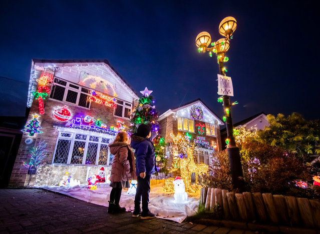People look at the Christmas display on Stone Brig Lane in Rothwell, Yorkshire on December 2, 2019, as houses on the street are illuminated by Christmas lights during an event that has become know as the Stone Brig Lights. (Photo by Danny Lawson/PA Images via Getty Images)