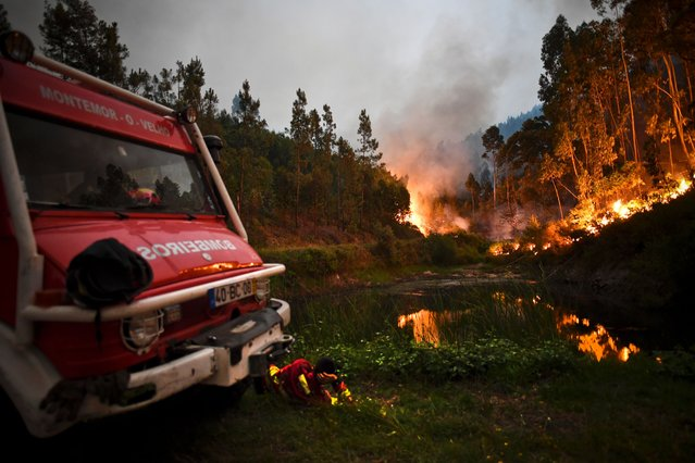A firefighter rests next to fire combat truck during a wildfire at Penela, Coimbra, central Portugal, on June 18, 2017. A wildfire in central Portugal killed at least 25 people and injured 16 others, most of them burning to death in their cars, the government said on June 18, 2017. Several hundred firefighters and 160 vehicles were dispatched late on June 17 to tackle the blaze, which broke out in the afternoon in the municipality of Pedrogao Grande before spreading fast across several fronts. (Photo by Patricia De Melo Moreira/AFP Photo)