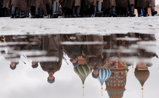 Participants are reflected in a puddle while marching near St. Basil's Cathedral during preparations for a military parade to mark the anniversary of a historical parade in 1941, when Soviet soldiers marched towards the front lines during World War Two, on Red Square in central Moscow, Russia November 7, 2019. (Photo by Maxim Shemetov/Reuters)