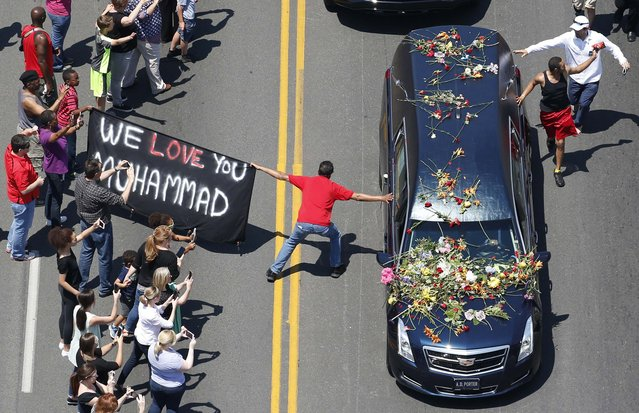 A well-wisher holding a banner touches the hearse carrying the remains of Muhammad Ali during the funeral procession for the three-time heavyweight boxing champion in Louisville, Kentucky, U.S., June 10, 2016. (Photo by Adrees Latif/Reuters)