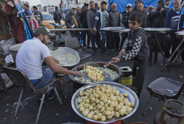 In this photo taken Sunday, December 8, 2019, a volunteer chef prepares to serve free portions of the popular sweets of Awamah, fried dough balls, to protester in the center of Baghdad, Iraq. (Photo by Nasser Nasser/AP Photo)