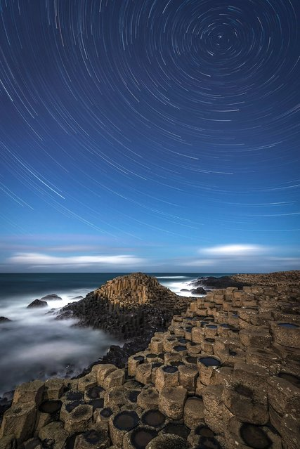 A Giant's Star Trail by Rob Oliver (UK). A composition of several images taken at the famed Giant's Causeway in Northern Ireland. Our planet's rotation draws the stars out into circles – considered to be the most perfect shape by ancient philosophers. Separated from the sky by the stark line of the horizon, the atomic symmetries of crystallized rock display themselves in the hexagonal columns of the Giant's Causeway. (Photo by Rob Oliver)