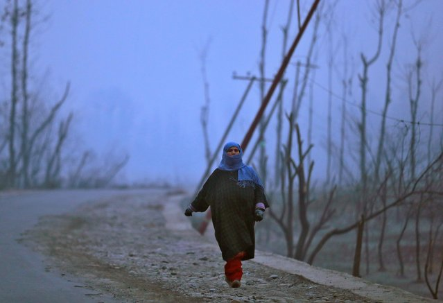 A woman walks along a road on a cold winter morning in Srinagar on January 2, 2020. (Photo by Danish Ismail/Reuters)