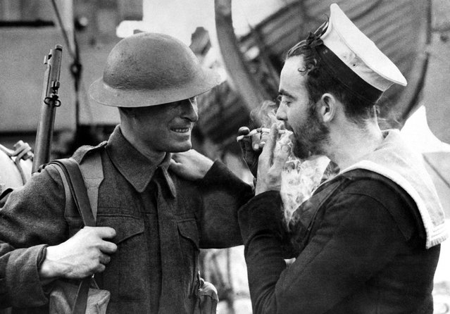 Two examples of Britain's war forces, a soldier in battle dress and a bearded Canadian sailor share a light at an English port, on January 14, 1941