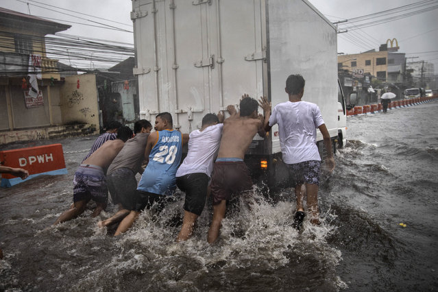 Residents help push a stalled van off a flooded highway during the onslaught of Typhoon Kammuri on December 3, 2019 in Lipa town, Batangas province, Philippines. Tens of thousands of residents have been evacuated as Typhoon Kammuri slammed into the Philippines' main island of Luzon. The powerful typhoon has forced hundreds of flights to be cancelled and has caused the Southeast Asian Games currently being held in the country to be postponed. (Photo by Ezra Acayan/Getty Images)
