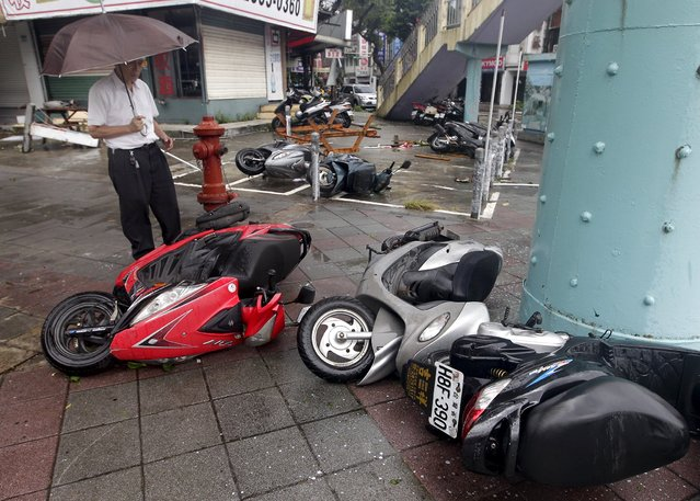 A man inspects motorcycles tipped over by strong wind from Typhoon Soudelor in Taipei, Taiwan, August 8, 2015. (Photo by Pichi Chuang/Reuters)