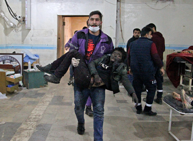 A member of the Syrian Violet Oragnization carries an injured boy at a makeshift hospital following a regime air strike on a vegetable market in Syria's last major opposition bastion of Idlib on January 15, 2020. Regime air strikes on Syria's last major opposition bastion killed at least nine civilians, striking bustling areas of Idlib city despite a fresh Russian-sponsored truce, a war monitor said. (Photo by Abdulaziz Ketaz/AFP Photo)