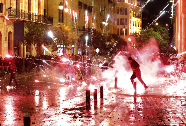 Anti-government protesters throw firecrackers at riot police during a demonstration against the new government, near Parliament Square, in Beirut, Lebanon, early Wednesday, January 22, 2020. A new Cabinet was announced in crisis-hit Lebanon late Tuesday, breaking a months-long impasse amid mass protests against the country's ruling elite and a crippling financial crisis, but demonstrations and violence continued. (Photo by Hussein Malla/AP Photo)