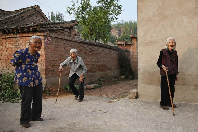 """Village women accompany Chinese former """"comfort woman"""" Hao Juxiang (R) as she poses for a picture outside their houses in Gucheng Town, Shanxi Province, China, July 16, 2015. (Photo by Kim Kyung-Hoon/Reuters)"""