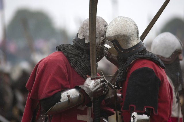 People dressed as knights take part in a reenactment of The Battle of Grunwald, in Grunwald July 12, 2014. The battle is thought of as the most important victory in Poland's history and was one of the biggest battles in Medieval Europe. 1300 history enthusiasts took part in the reenactment, which was watched by 15,000 spectators, using self-made weapons and costumes. (Photo by Filip Klimaszewski/Reuters)