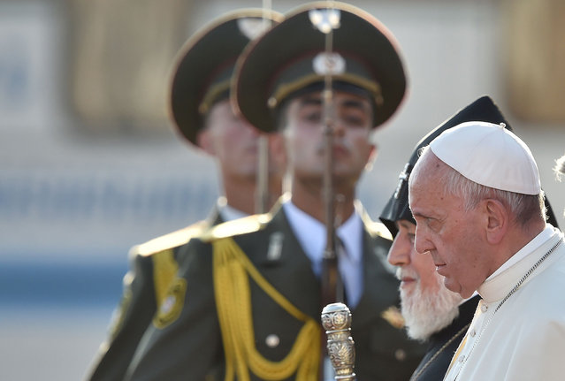Pope Francis, flanked by Catholicos of All Armenians Karekin II, walks past honour guards to board a plane for Rome at Yerevan's Zvartnots Airport on June 26, 2016. (Photo by Alexander Nemenov/AFP Photo)