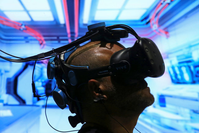 Pablo Holcer tests out a VR system made by Neurable that allows the user to control with their thoughts as the EEG headset interprets thoughts into actions in the VR environment at SIGGRAPH 2017 in Los Angeles, California, July 31, 2017. (Photo by Mike Blake/Reuters)