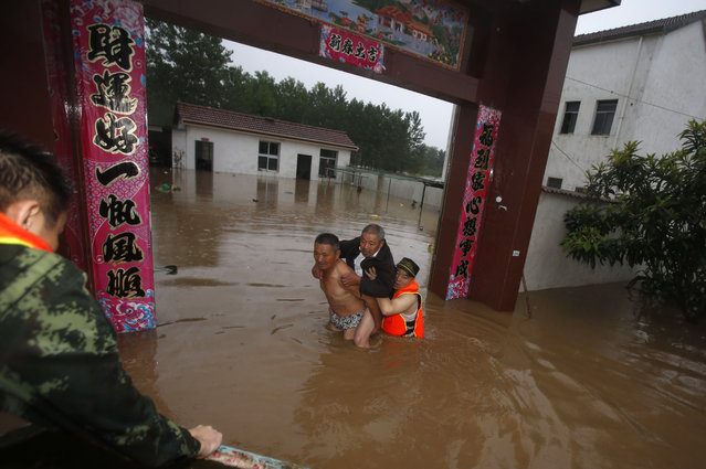 This picture taken on July 1, 2016 shows a man being rescued from a flooded house in Xinzhou, in China's central Hubei province. Authorities on July 2 issued an orange alert for heavy rain expected in central and southern parts of China in coming days. (Photo by AFP Photo/Stringer)