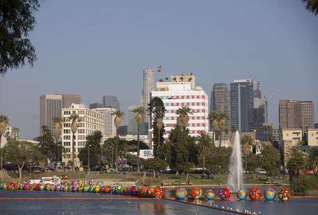 "Inflated spheres are pictured in MacArthur Park Lake, with the downtown skyline in the background, during the installation of Portraits of Hope's exhibition ""Spheres at MacArthur Park"" in Los Angeles, California August 21, 2015. (Photo by Mario Anzuoni/Reuters)"