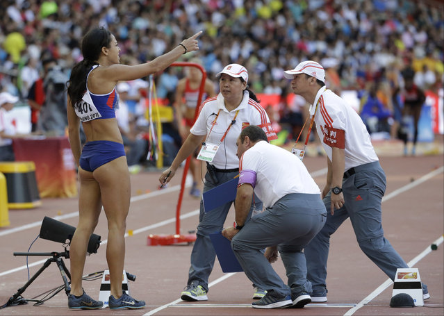 Britain's Katarina Johnson-Thompson, left, disputes the foul jump she was given with officials, as she competes in the women's long jump heptathlon at the World Athletics Championships at the Bird's Nest stadium in Beijing, Sunday, August 23, 2015. (Photo by Lee Jin-man/AP Photo)