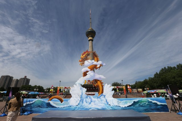 A 3D painting of a dragon gets put in front of China Television Tower during the China's largest 3D painting show on August 6, 2014 in Beijing, China. There are more than 230 3D paintings at the exhibition which occupies the total area of 15,000 square meters. (Photo by ChinaFotoPress/ChinaFotoPress via Getty Images)