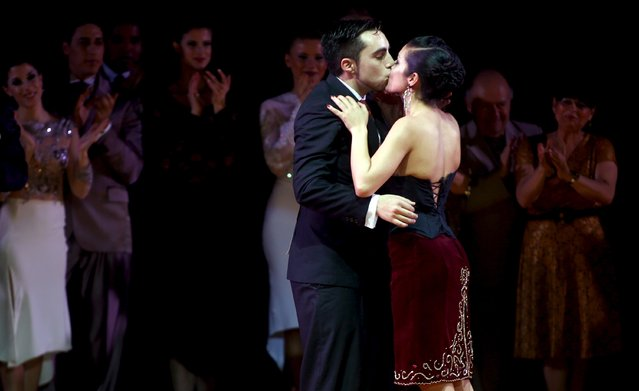 Jonathan Saavedra (C) and Clarisa Aragon from Argentina, representing the Argentine city of Cordoba, kiss after winning the Tango World Championship in Salon style, in Buenos Aires August 26, 2015. (Photo by Marcos Brindicci/Reuters)