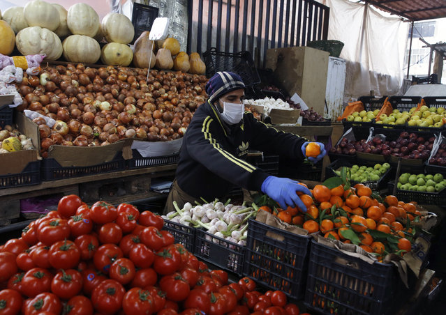 Syrian Sami Jawabreh wears a mask and gloves, as he rearranges fruits on display for sale at his shop, in Beirut, Lebanon, Wednesday, March 18, 2020. Lebanon has been taking strict measures to limit the spread of the coronavirus closing restaurants and nightclubs as well as schools and universities. For most people, the new coronavirus causes only mild or moderate symptoms. For some it can cause more severe illness. (Photo by Bilal Hussein/AP Photo)