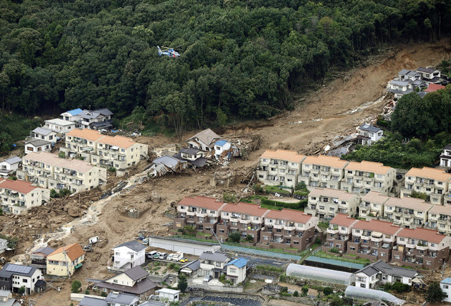 In this aerial photo, a rescue helicopter hovers  over an area devastated by a massive landslide in Hiroshima, western Japan, Wednesday, August 20, 2014. A several people died and at least a dozen are missing after rain-sodden hills in the outskirts of Hiroshima gave way early Wednesday in several landslides. (Photo by AP Photo/Kyodo News)