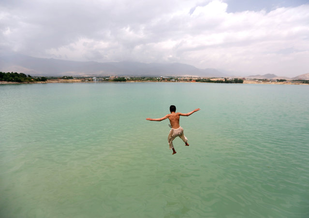 An Afghan boy jumps for a swim at Qargha lake in Kabul, Afghanistan June 29, 2016. (Photo by Mohammad Ismail/Reuters)