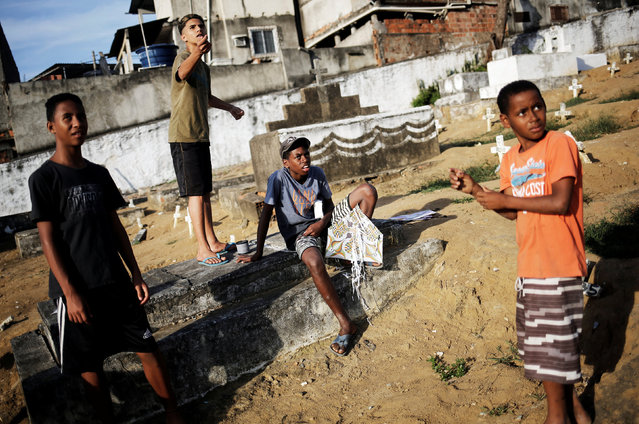 A boy (2nd L) flies his kite as his friends watch, in a cemetery in the Vila Operaria Favela of Rio de Janeiro, Brazil, July 9, 2016. (Photo by Nacho Doce/Reuters)