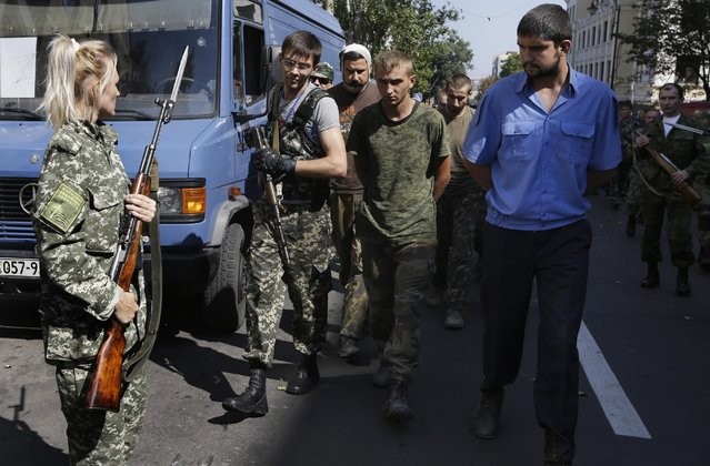 Pro-Russian rebels escort captured Ukrainian army prisoners in a central square in Donetsk, eastern Ukraine, Sunday, August 24, 2014. Ukraine has retaken control of much of its eastern territory bordering Russia in the last few weeks, but fierce fighting for the rebel-held cities of Donetsk and Luhansk persists. (Photo by Sergei Grits/AP Photo)