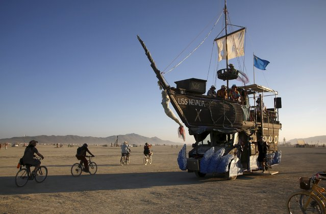 """The USS Nevada, a Mutant Vehicle, carries participants on the Playa during the Burning Man 2015 """"Carnival of Mirrors"""" arts and music festival in the Black Rock Desert of Nevada, August 31, 2015. (Photo by Jim Urquhart/Reuters)"""
