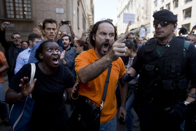 Demonstrators react as they try to stop the car carrying Xavier Puig, a senior at the Department of External Affairs, Institutional Relations and Transparency of the Catalan Government office, after he was arrested by Guardia Civil officers in Barcelona, Spain, Wednesday, September 20, 2017. Spanish police arrested 12 people Wednesday in raids on offices of the regional government of Catalonia, news reports said, intensifying a crackdown on the region's preparations for a secession vote that Spain says is illegal. (Photo by Emilio Morenatti/AP Photo)
