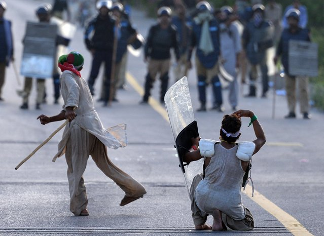 Pakistani supporters of Canadian cleric Tahir ul Qadri and cricket-turned politician Imran Khan face riot police during an anti-government protest in Islamabad on September 1, 2014. (Photo by Aamir Qureshi/AFP Photo)