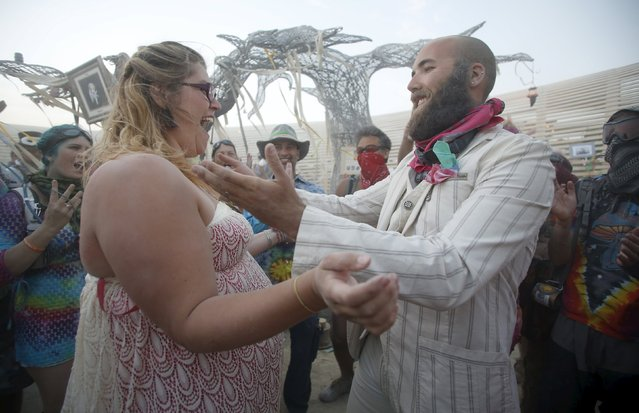 "Shandi Trolson (L) and Jordan Lenaburg celebrate as they are married during a wedding ceremony at the Burning Man 2015 ""Carnival of Mirrors"" arts and music festival in the Black Rock Desert of Nevada, September 2, 2015. (Photo by Jim Urquhart/Reuters)"
