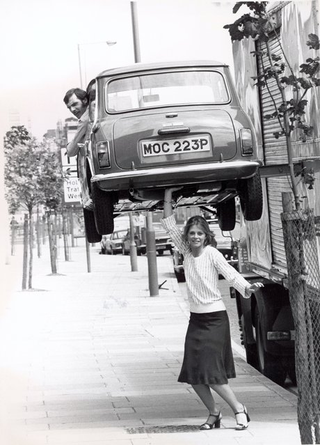 """American actress Lindsay Wagner appears to hold a man in a Mini above her head during a visit to Britain to promote the television series """"The Bionic Woman"""", London, England, June 7, 1976. The car was actually hoisted by a care, which was out of sight of the camera. (Photo by Express Newspapers)"""