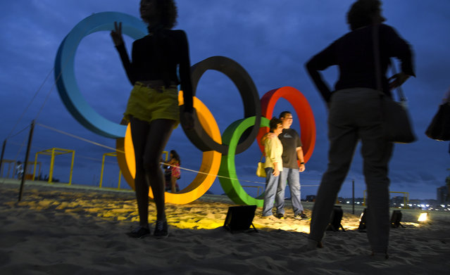 Visitors take their picture in front of the Olympic rings on Copacabana beach on August 3, 2016 in Rio De Janeiro, Brazil. (Photo by Jonathan Newton/The Washington Post)