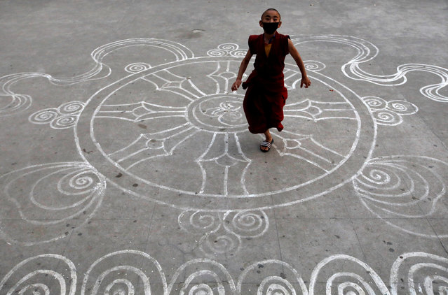 A novice monk wearing a protective mask runs at the premises of a monastery during the eighteenth day of the lockdown imposed by the government amid concerns about the spread of coronavirus disease (COVID-19) outbreak, in Kathmandu, Nepal on April 10, 2020. (Photo by Navesh Chitrakar/Reuters)