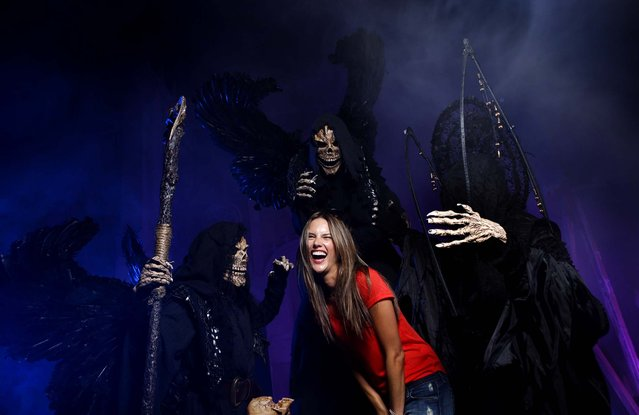 Victoria's Secret model Alessandra Ambrosio poses with members of The Iniquitus, patrons of death, during a sneak peek at Universal Orlando's Halloween Horror Nights 22, on September 26, 2012. (Photo by Kevin Kolczynski/Universal)