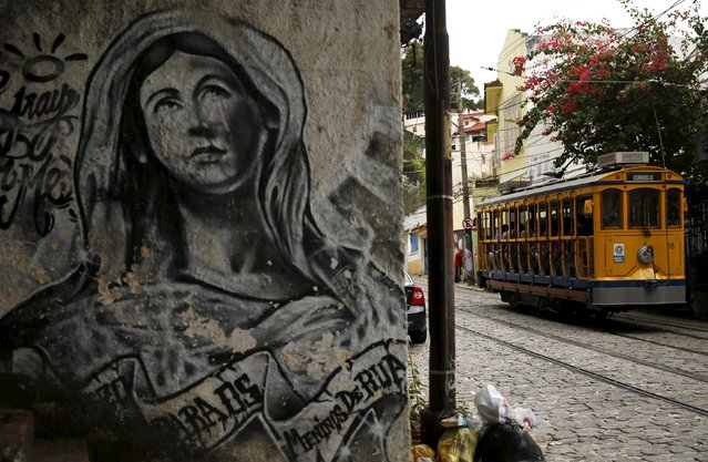 The bonde, the typical tram line in Santa Teresa neighborhood, is pictured running past graffiti in Rio de Janeiro, Brazil, September 9, 2015. (Photo by Pilar Olivares/Reuters)