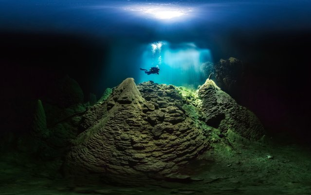 """Cave Diver, Anhumas Abyss, Bonito, Brazil: The Anhumas Abyss is an underground cavern with a crystal-clear lake below, more than 260 feet (79 m) deep. A visitor must enter through a narrow opening at the top of the chamber and rappel into the cave. Snorkeling and scuba diving in the lake reveal amazing scenery. Distinctive, conical limestone stalagmites and stalactites occupy the lake and the surrounding area, some reaching 65 feet (20 m) high. """"One must rappel about 235 feet (72 m) to get down into this deep lake. The photo was taken at a depth of 50 feet (15 m). It was a challenge to create the image because of the high contrast, plus the diver could not see into the darkness, making communication impossible"""". (Photo by Marcio Cabral/Nature's Best Photography Awards 2017)"""