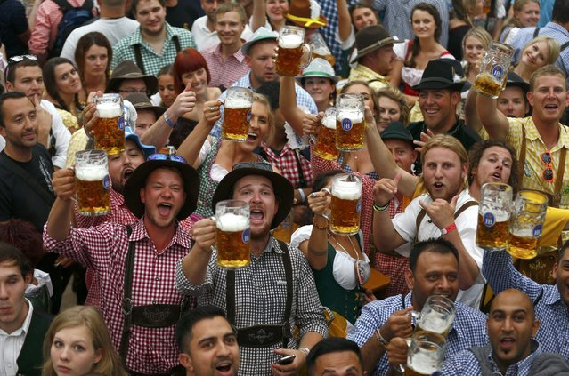 Visitors toast with their one-liter beer mugs during the opening day of the 181st Oktoberfest in Munich September 20, 2014. Millions of beer drinkers from around the world will come to the Bavarian capital over the next two weeks for the Oktoberfest, which starts today and runs until October 5. (Photo by Michael Dalder/Reuters)